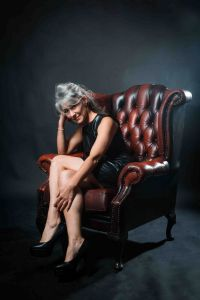 A portrait of grey hair model Valeria Sechi sitting on a leather armchair