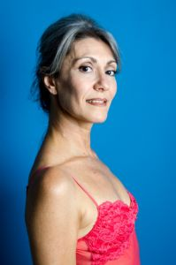 A portrait of grey hair model Valeria Sechi with a blue background