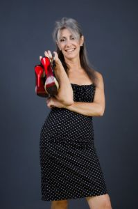 A portrait of grey hair model Valeria Sechi with a pois dress and red shoes in hand