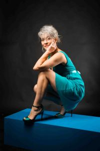 A portrait of grey hair model Valeria Sechi wth a turquoise dress