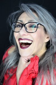 A portrait of grey model Valeria Sechi wearing black eyeglasses and smiling