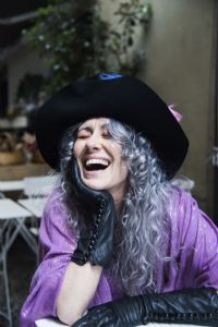Grey hair model Valeria Sechi laughing and wearing gloves and a hat with feathers