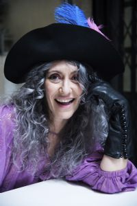Grey hair model Valeria Sechi smiling and wearing gloves and a hat with feathers