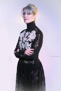 Grey hair model Valeria Sechi wearing a dress with floral embroidery