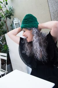 Grey hair model Valeria Sechi wearing a green hat