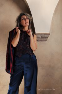 Grey hair model Valeria Sechi wearing a jacket and blue trousers