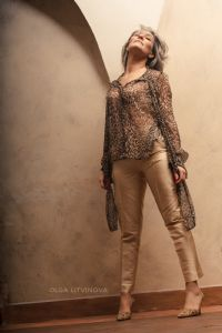 Grey hair model Valeria Sechi wearing a leopard print shirt and golden trousers