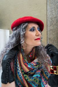Grey hair model Valeria Sechi wearing a red hat and black gloves