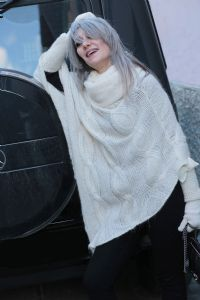 Grey hair model Valeria Sechi wearing a white wool sweater and gloves