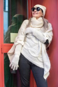 Grey hair model Valeria Sechi wearing a white wool sweater gloves and sunglasses