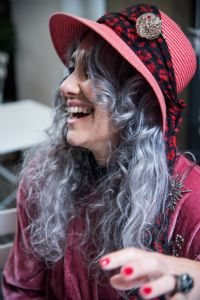Grey hair model Valeria Sechi laughing and wearing pink hat and dress