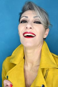 Grey hair model Valeria Sechi wearing a yellow leather jacket
