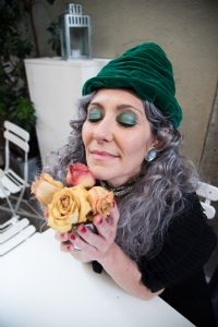 Grey hair model Valeria Sechi with yellow roses wearing a green hat